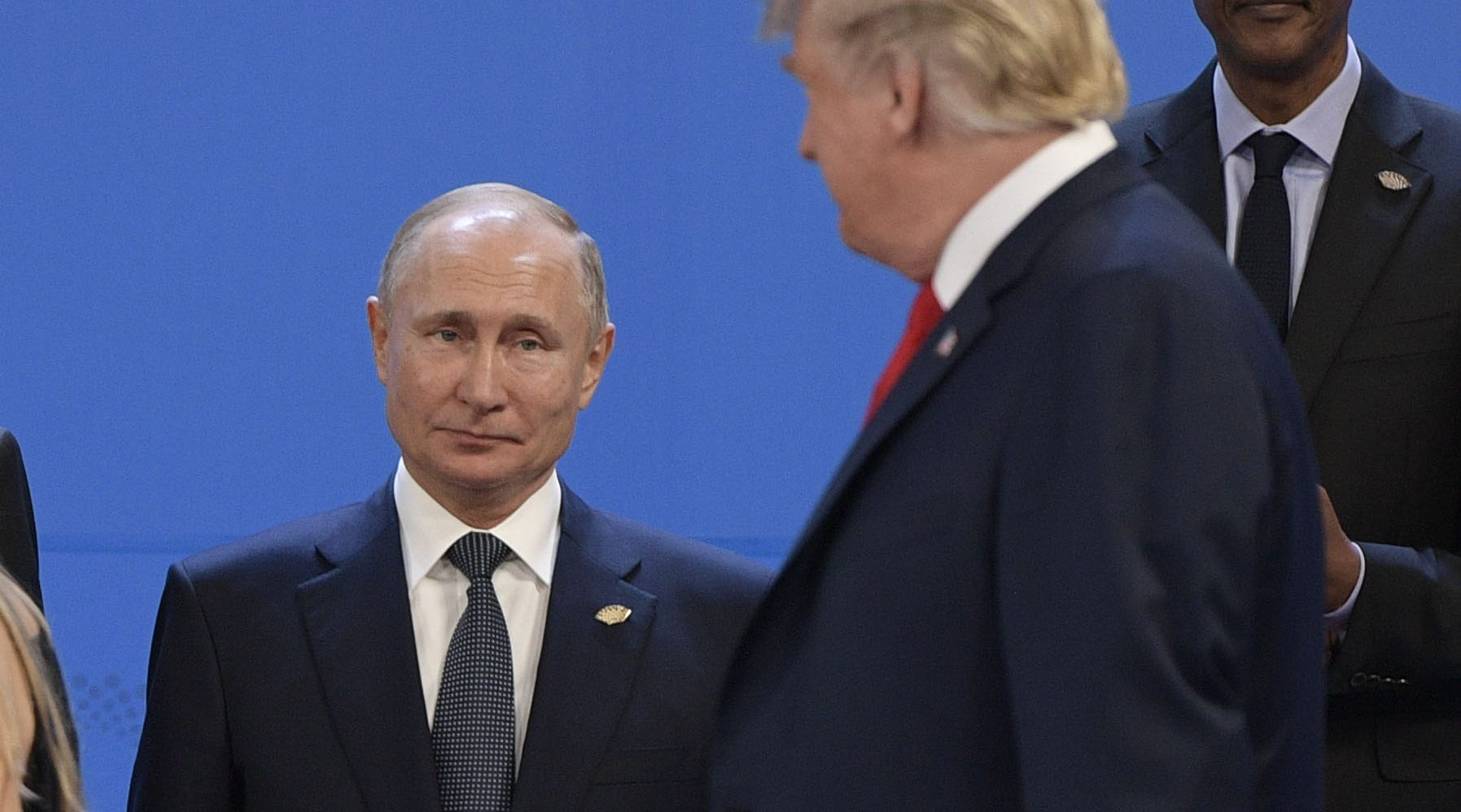 President Donald Trump, looks at Russia's President Vladimir Putin as they prepare for a group photo, during the G-20 Leaders' Summit in Buenos Aires, on Nov. 30, 2018.