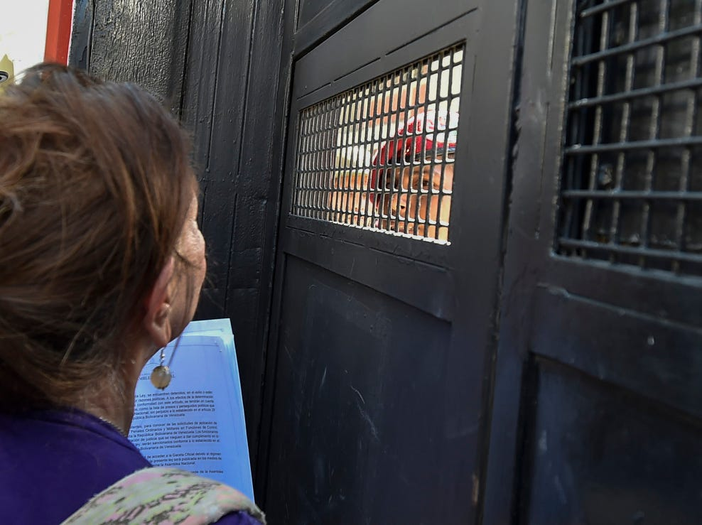 "An opposition supporter delivers copies of amnesty measures to anyone in the military who disavows President Nicolas Maduro, at a military headquarters in Caracas on Jan. 27, 2019.  Venezuela's National Assembly head and self-proclaimed ""acting president"" Juan Guaido, who has galvanized a previously divided opposition, is offering an amnesty approved by the opposition-controlled National Assembly to anyone in the military who disavows President Nicolas Maduro, even suggesting amnesty for Maduro himself."