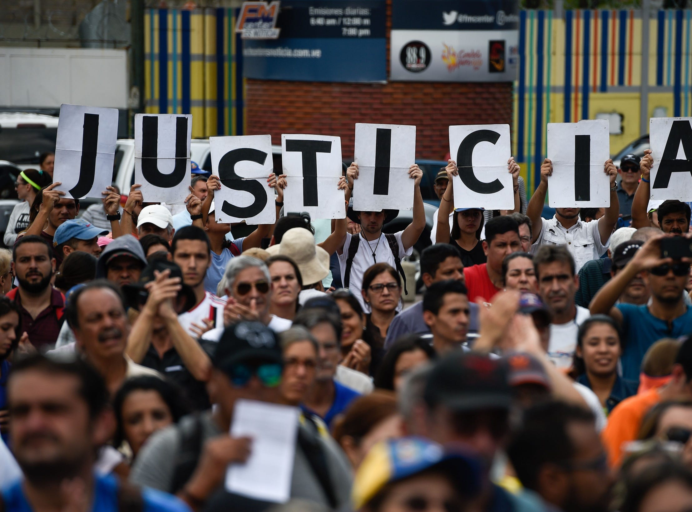 "Venezuelan opposition supporters holding up letters reading ""Justice"" gather to listen to the head of Venezuela's National Assembly and the country's self-proclaimed ""acting president"" Juan Guaido, during a rally in Caracas, on Jan. 26, 2019."