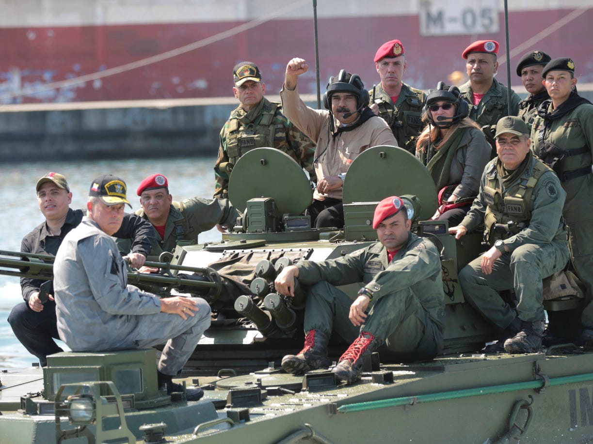Venezuelan President Nicolas Maduro raises his fist from an amphibious tank as he poses for photos alongside first lady Cilia Flores and Defense Minister Vladimir Padrino Lopez, center right, at the Naval base in Puerto Cabello, Venezuela, Sunday, Jan. 27, 2019.