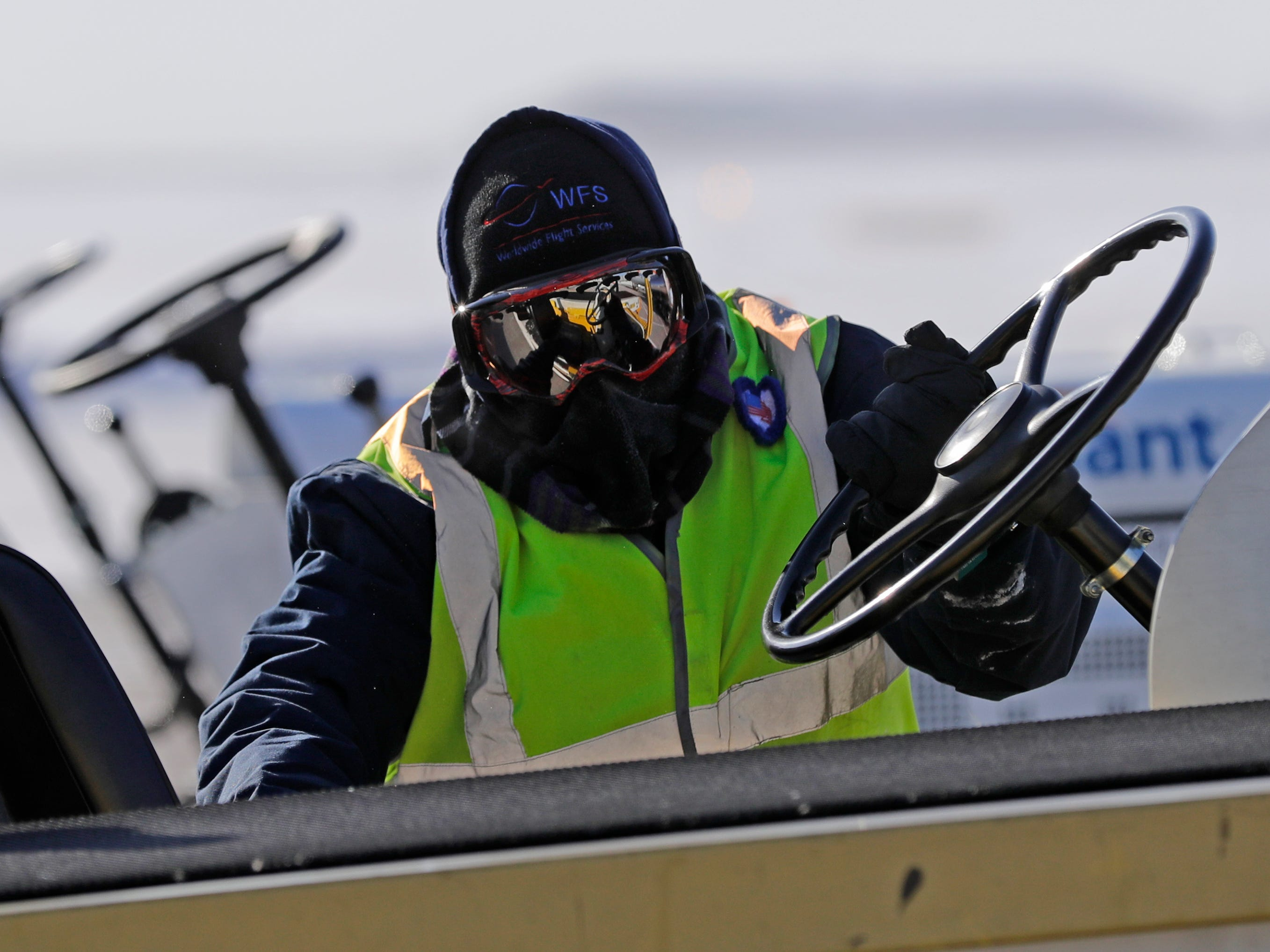 A Worldwide Flight Services employee braves frigid temperatures and high winds to remove luggage from an arriving Allegiant Airlines jet Jan. 30, 2019, at the Appleton International Airport in Greenville, Wis.