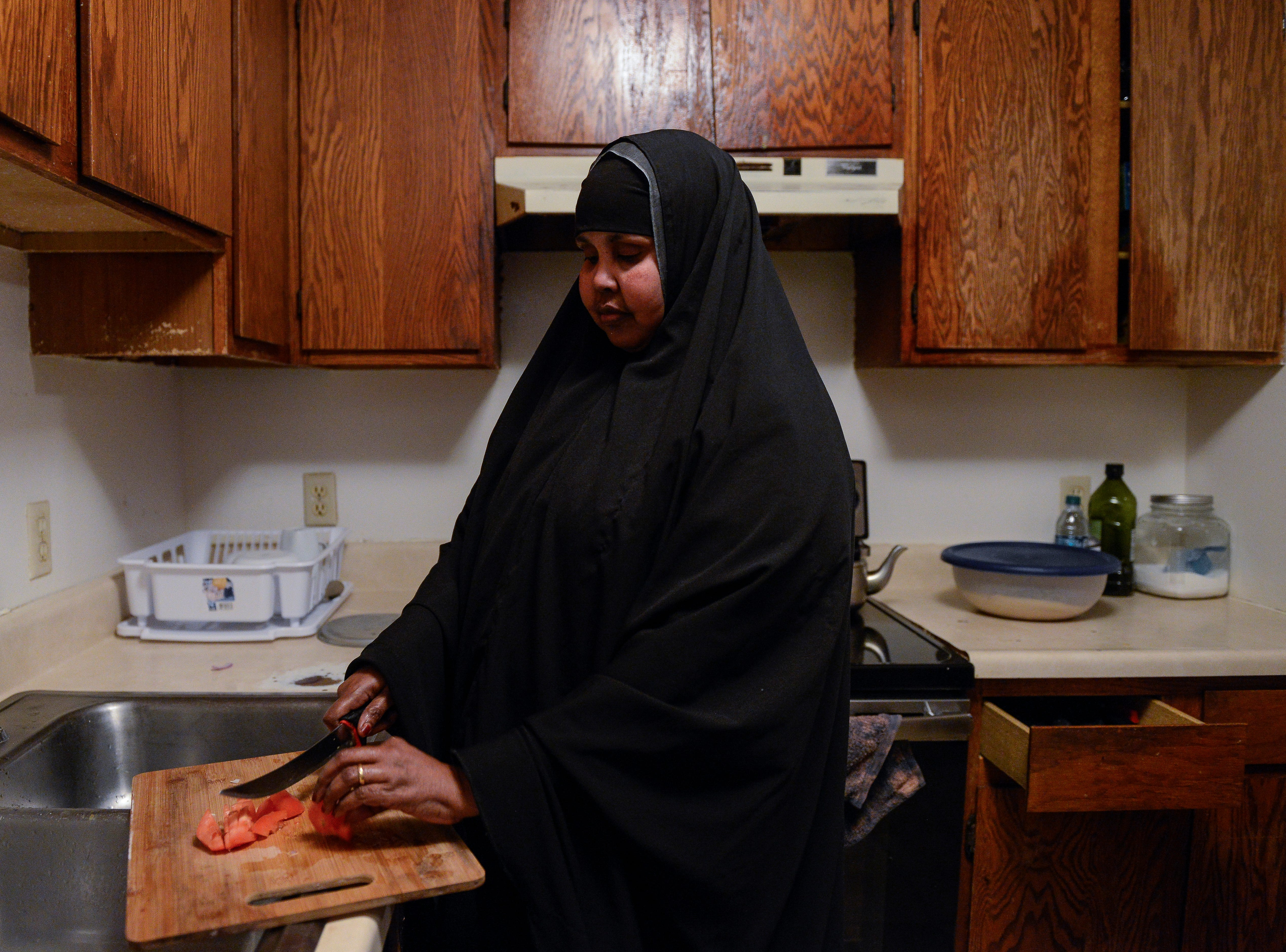 Deeja Mubafak, who moved to Garden City from Somalia in 2006, makes breakfast in her apartment before heading to her job at the Tyson Fresh Meats meatpacking plant on Wednesday, Jan. 23, 2019.