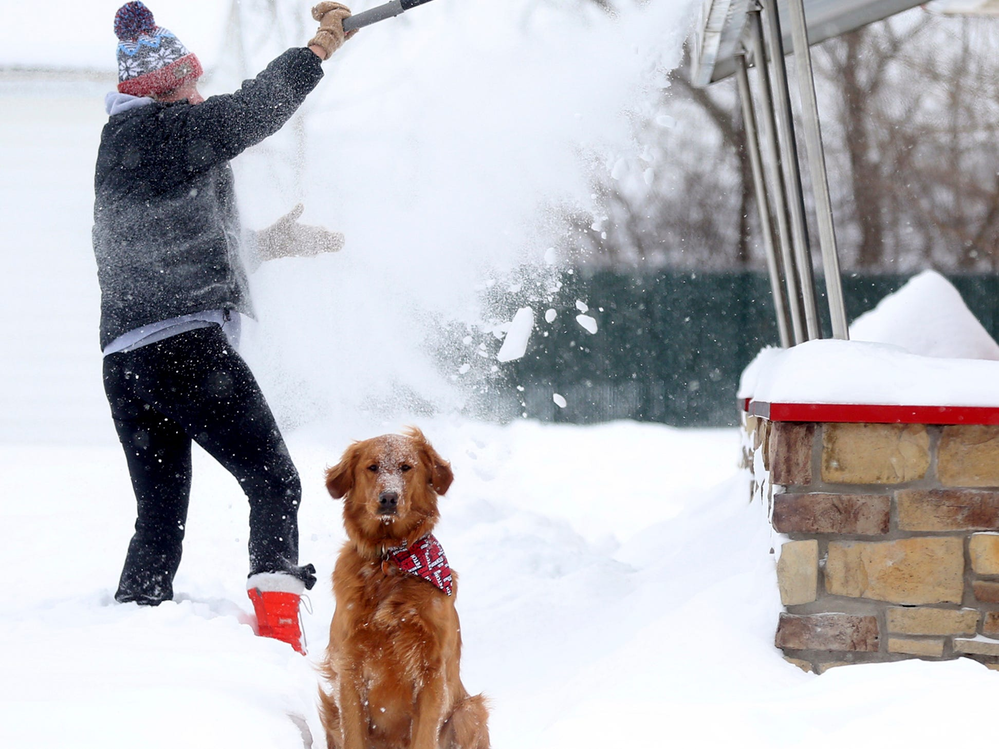 Vicki Blake clears snow from an awning on Dairy Queen while his dog Wrigley stands by in Dubuque, Iowa on Jan. 28, 2019.
