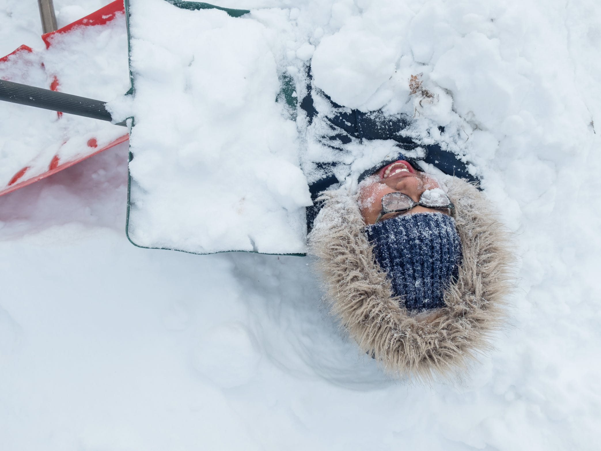 Jan 29, 2019; Flint, MI, USA; Ayanna Fulton of Flint reacts to the cold as her brother Dramell Fulton Jr. adds snow while burying her outside of their house on Billings St. while home on their second snow day. Mandatory Credit: Ryan Garza/Detroit Free Press via USA TODAY NETWORK ORIG FILE ID:  20190129_gma_usa_007.jpg