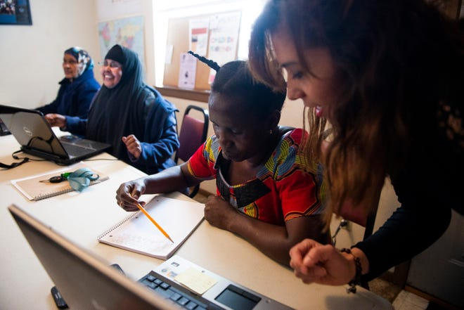 Kansas State Research and Extension nutrition education instructor Silvia Villatoro, right, helps Luiza Bandegeya learn to write at LiveWell Neighborhood Learning Center. The learning center helps refugees and immigrants learn English, learn to read and write and with other life skills.
