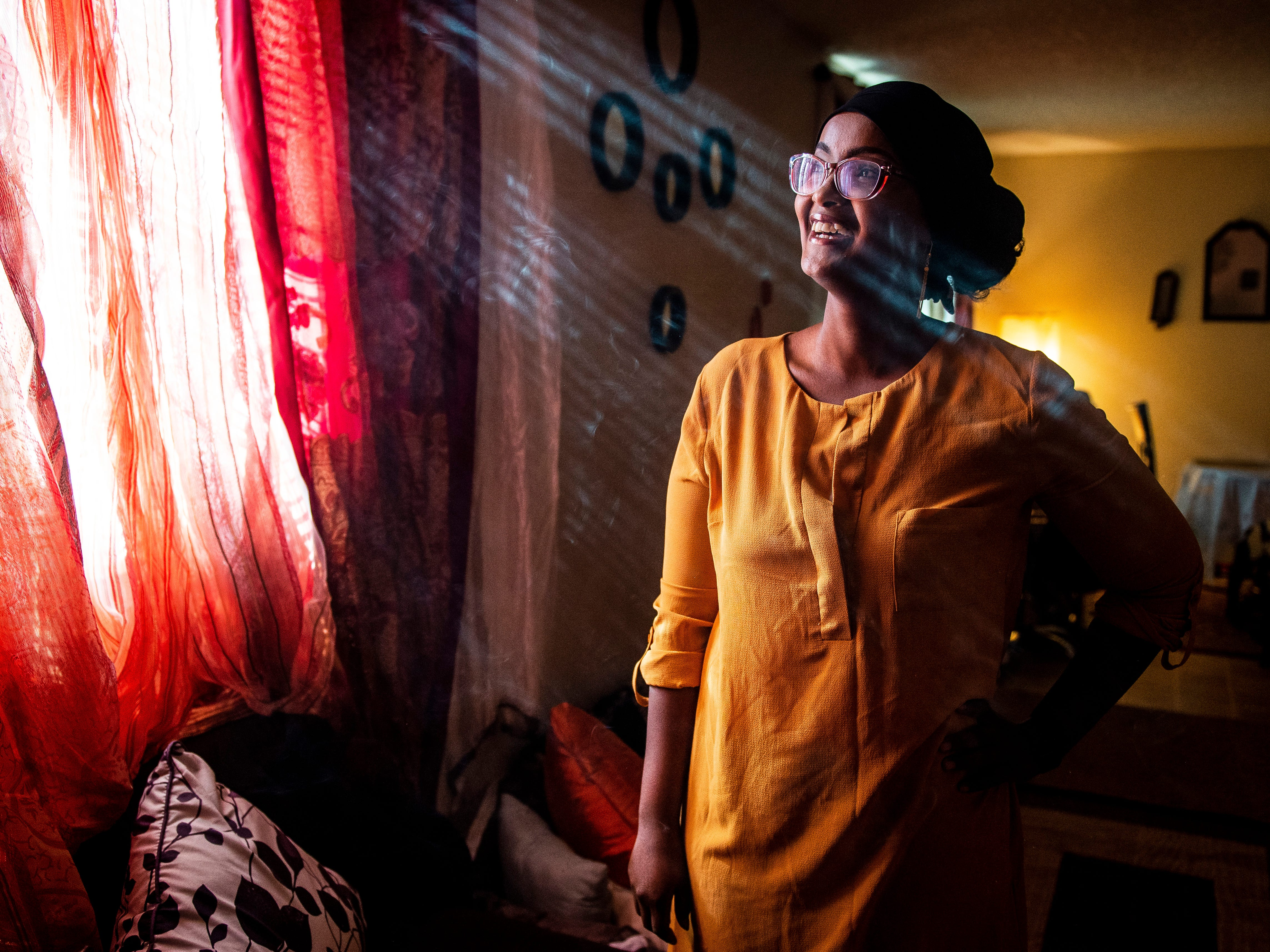Wrapped in smoke from homemade incense, Ifrah Ahmed, who was born in Kenya to Somali refugees, stands for a portrait in her Garden City apartment  Wednesday, Jan. 23, 2019. Ahmed, who now works at the Tyson Fresh Meats meatpacking plant, has lived in the US since 2010.