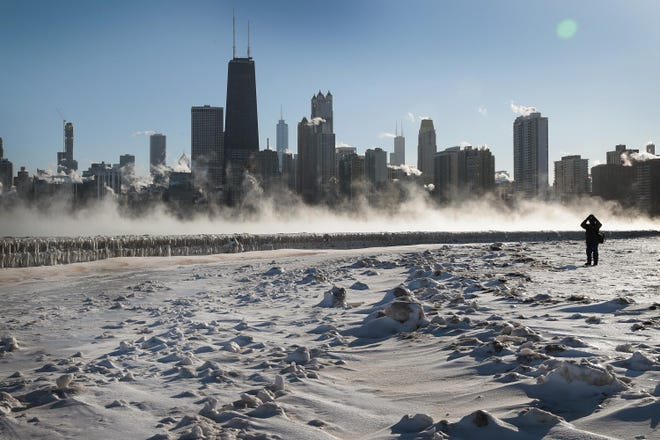 A visitor takes a picture of the Chicago skyline along the city's lakefront as temperature hung around -20 degrees on Jan. 30, 2019.