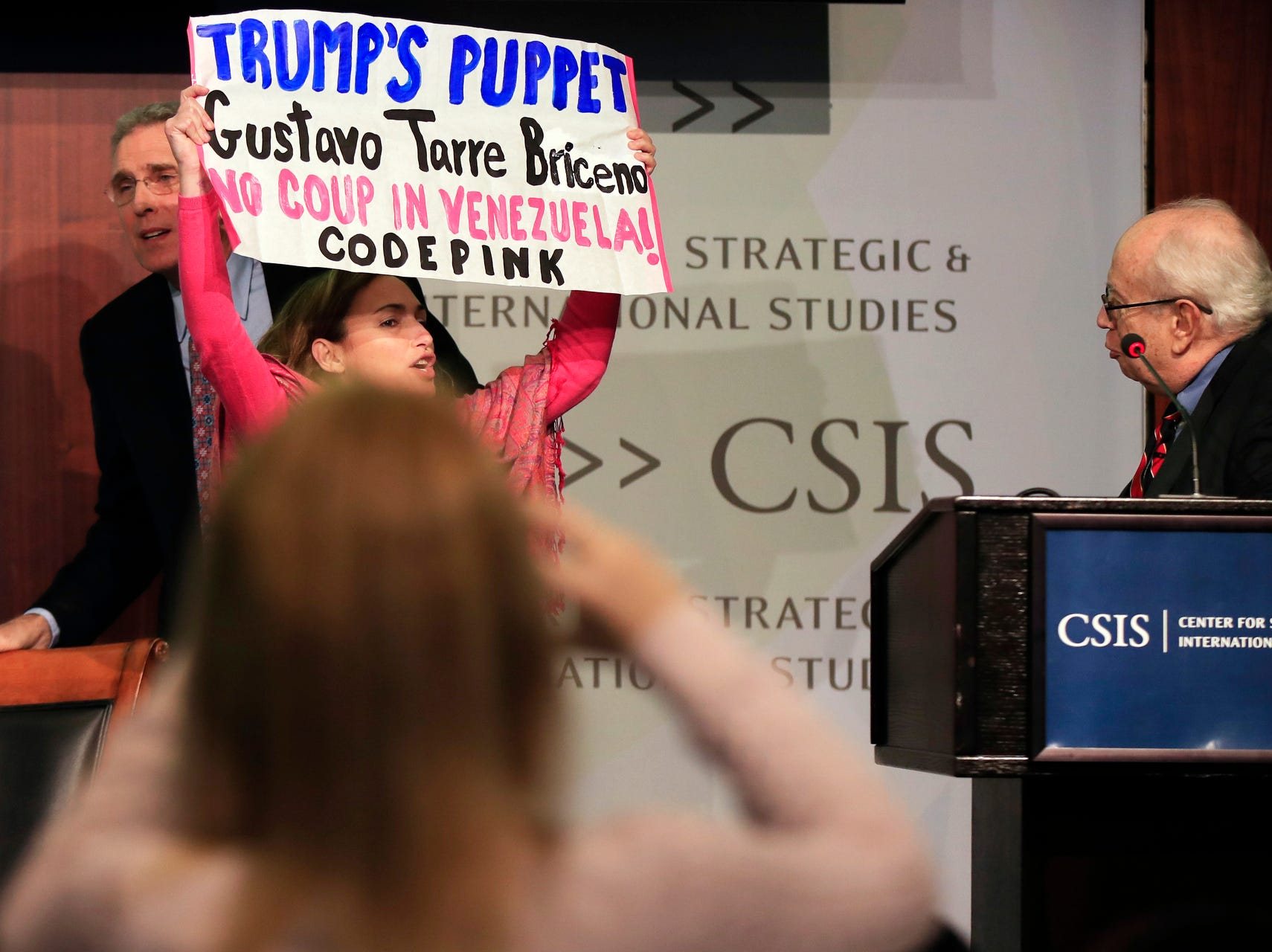 Gustavo Tarre, designated Venezuelan ambassador to the Organization of American States, appointed by Venezuelan opposition leader Juan Guaido, right, looks at a protestor wave a banner on stage during a panel discussion at the Center for Strategic and International Studies in Washington, on Tuesday,.