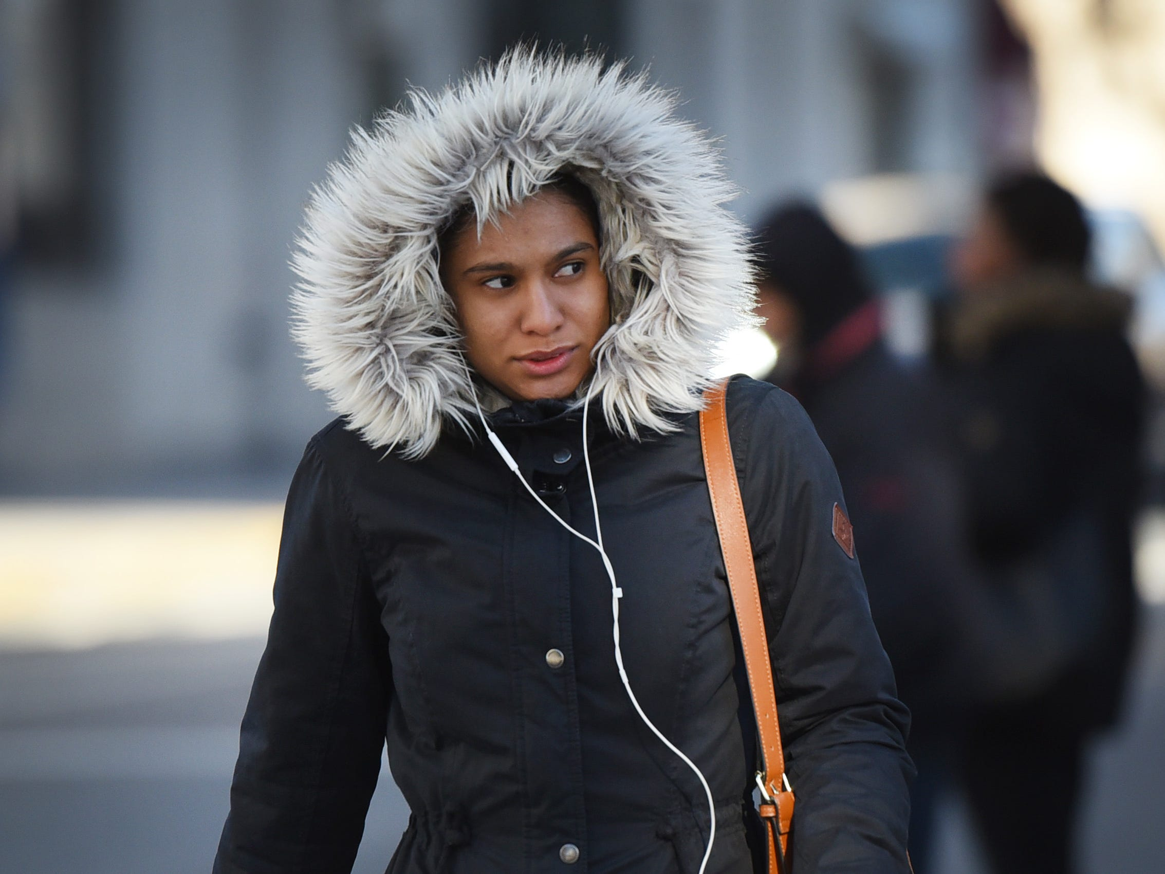 As the temperatures plummet, a woman braves the cold as she crosses the street in Paterson, NJ., Jan 30, 2019.