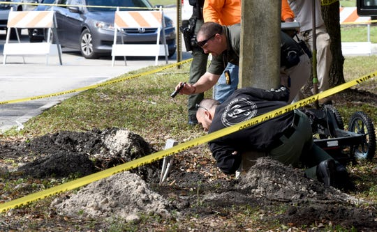 FBI and Pembroke Pines Police investigate a tunnel by a possible would-be bank robber which was discovered beneath the entrance to the Flamingo Pines shopping plaza Wednesday, Jan. 30, 2019, in Pembroke Pines, Fla. The tunnel stretched from a nearby wooded area towards the Chase bank branch in the plaza.