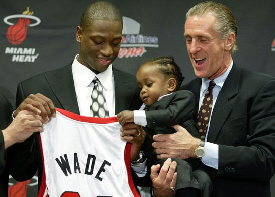 Dwyane Wade gets a little help holding up his jersey from his son Zaire, in 2003.