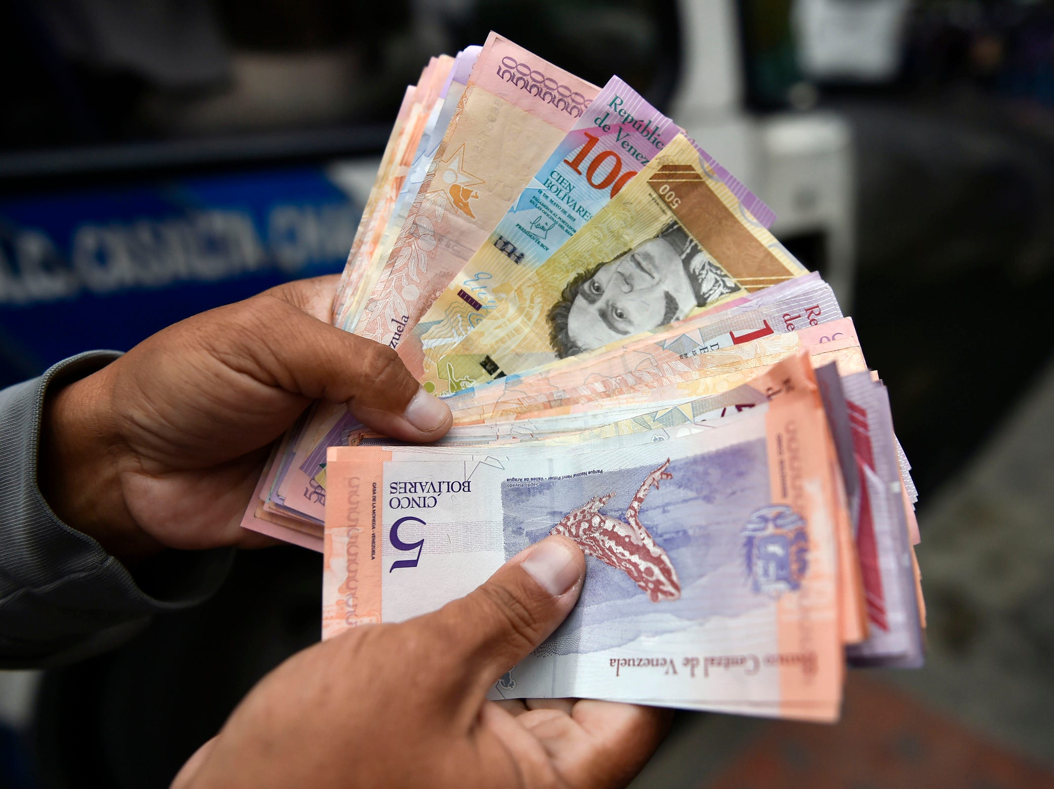 A man counts Bolivar bills in a street of Caracas, Tuesday. Venezuela devalued its currency by almost 35 percent on Monday to bring it into line with the exchange rate of the dollar on the black market. The exchange rate is now fixed at 3,200 bolivars to the dollar, almost matching the 3,118.62 offered on the dolartoday.com site that acts as the reference for the black market.