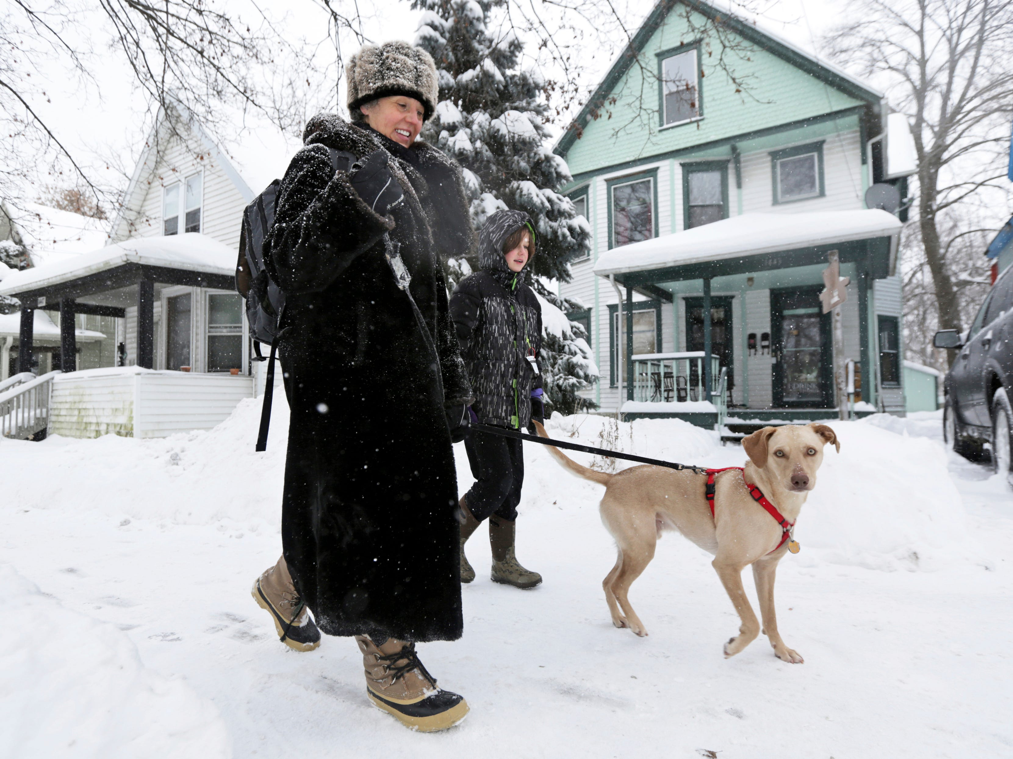 Marlisa Kopenski Condon walks to work with her son, Rex Condon, 10, and their dog, Coconut, during a winter storm in Madison, Wis. on, Jan. 28, 2019.