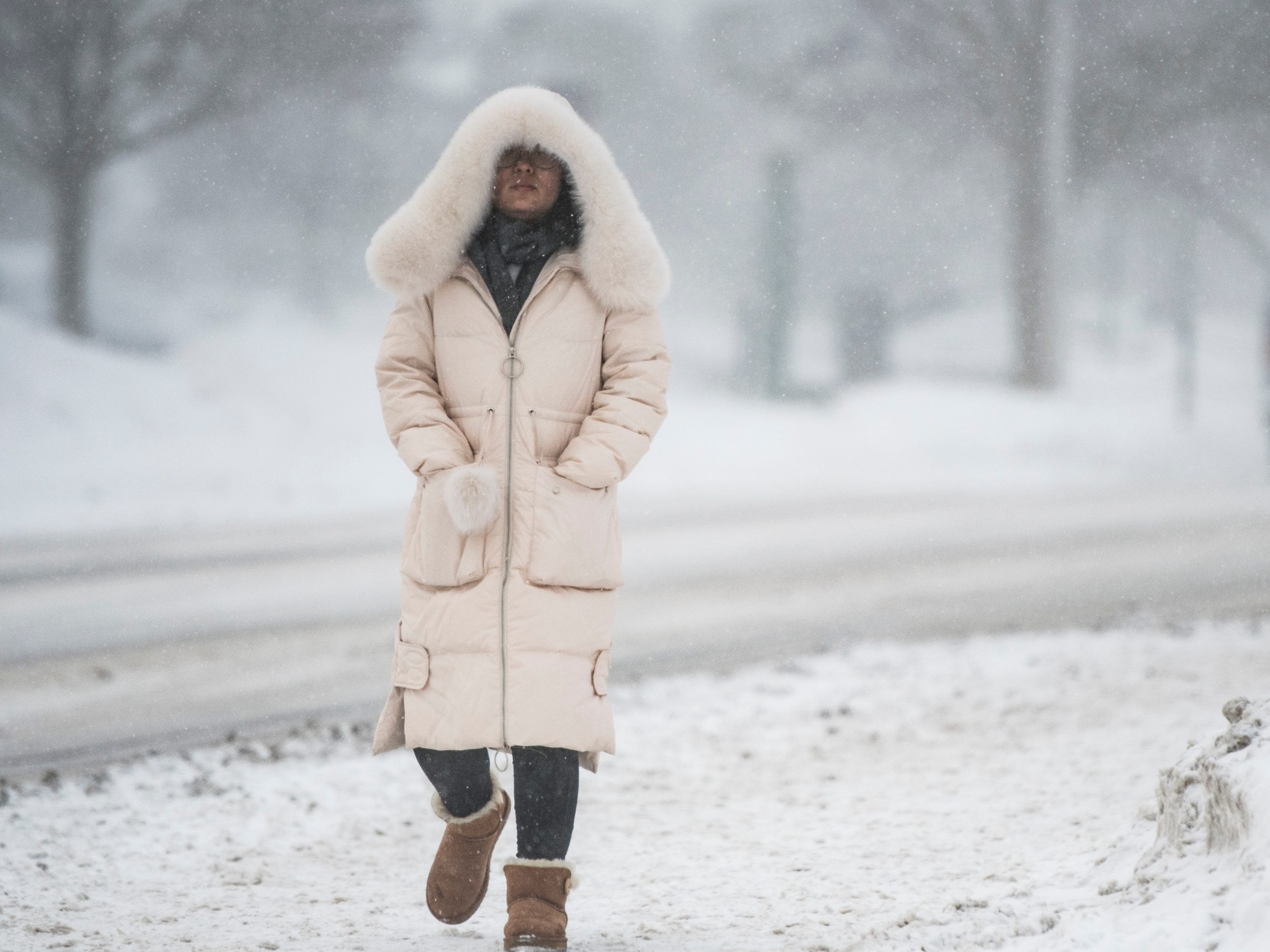 A woman heads across the campus of Michigan State University Jan. 29, 2019, in East Lansing.  MSU has called off classes tomorrow due to bitter temperatures.