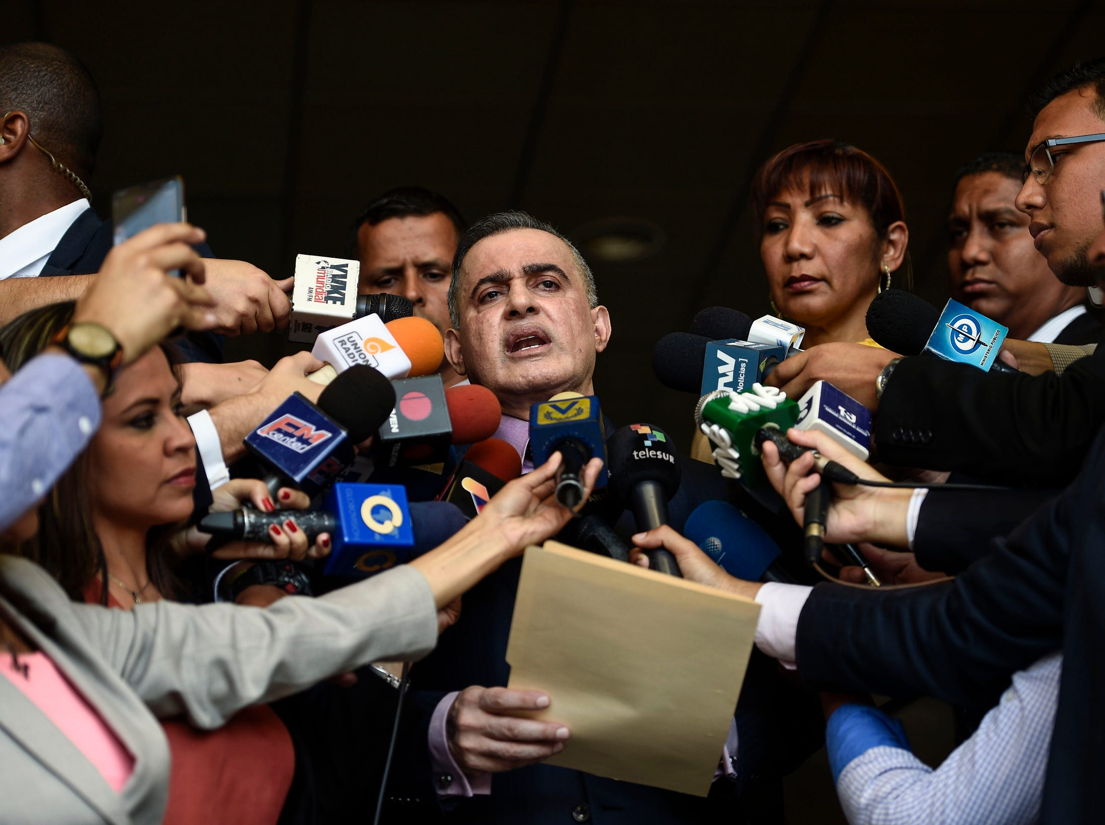 "Venezuelan Prosecutor Tarek William Saab (C), delivers a statement at the Supreme Court of Justice in Caracas to announce he has asked the Supreme Court to bar Venezuela's National Assembly head and self-proclaimed ""acting president"" Juan Guaido, from leaving Venezuela and to freeze his assets, on Tuesday."