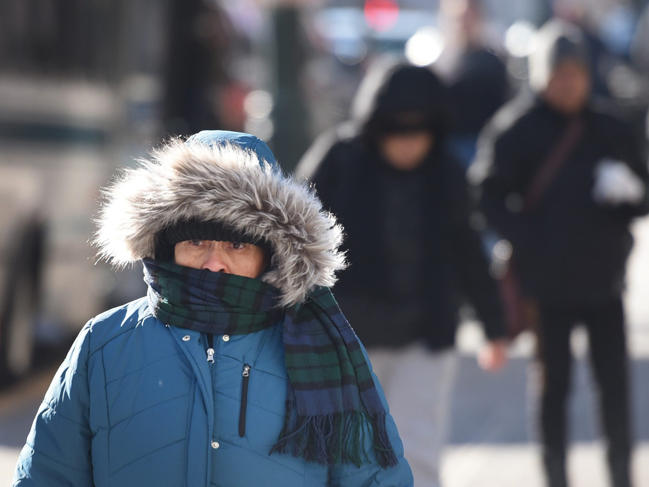 As the temperatures plummet, a woman braves the cold as she covers her face with a scarf in Paterson, NJ., Jan 30, 2019.
