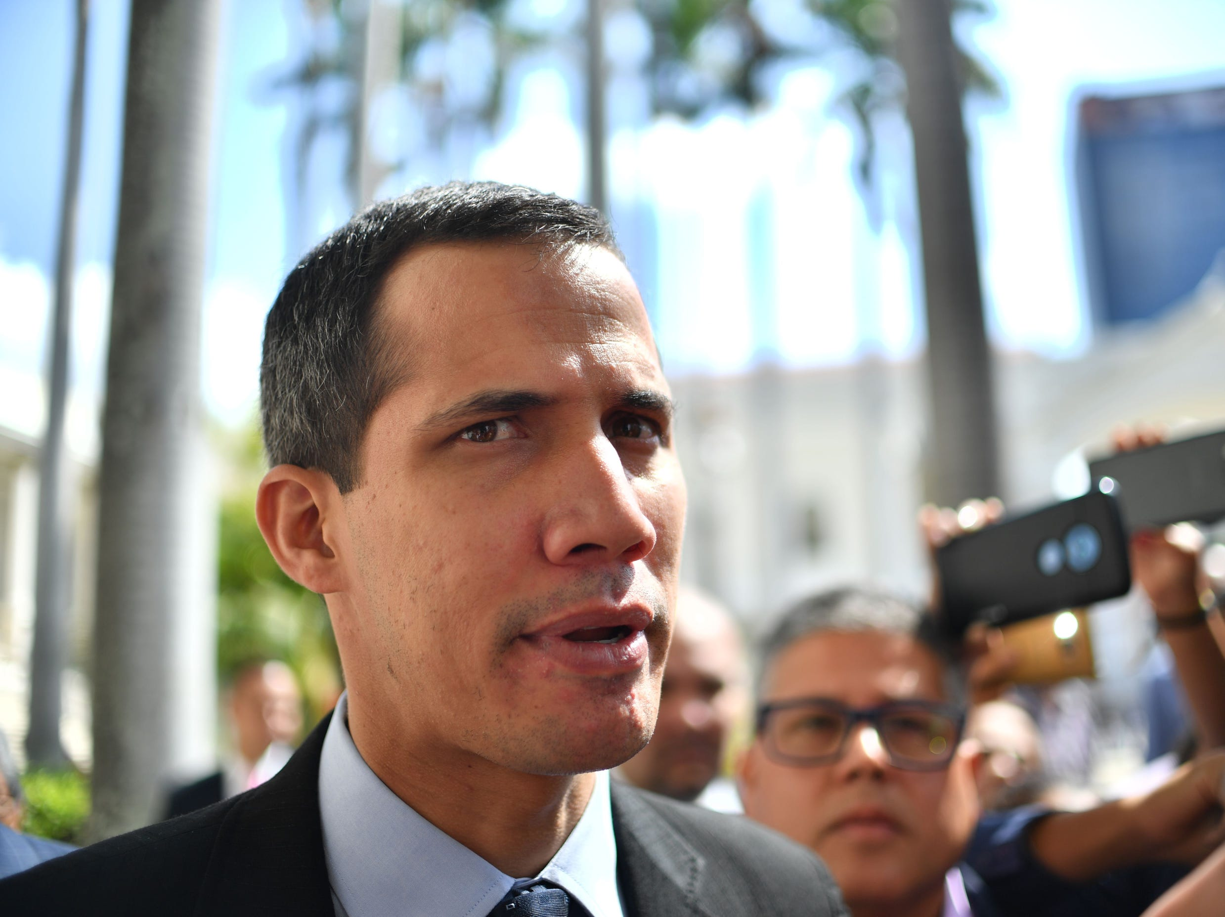 "National Assembly head and self-proclaimed ""acting president"" Juan Guaido, talks to journalists upon arrival at the National Assembly in Caracas, Tuesday."