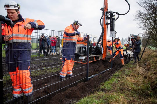 Workers erect a fence along Denmark's border with Germany at Padborg, Denmark, on Monday, Jan. 28, 2019. Denmark has begun erecting a 70-kilometer (43.4-mile) fence along the German border to keep out wild boars in an attempt to prevent the spread of African swine fever, which could jeopardize the country's valuable pork industry.