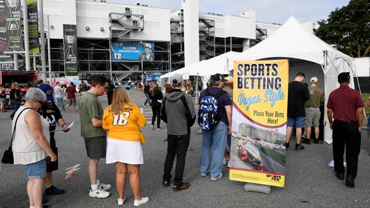 Fans line up next to a tent kiosk for legalized sports betting at Dover International Speedway before the October 2018 playoff race.