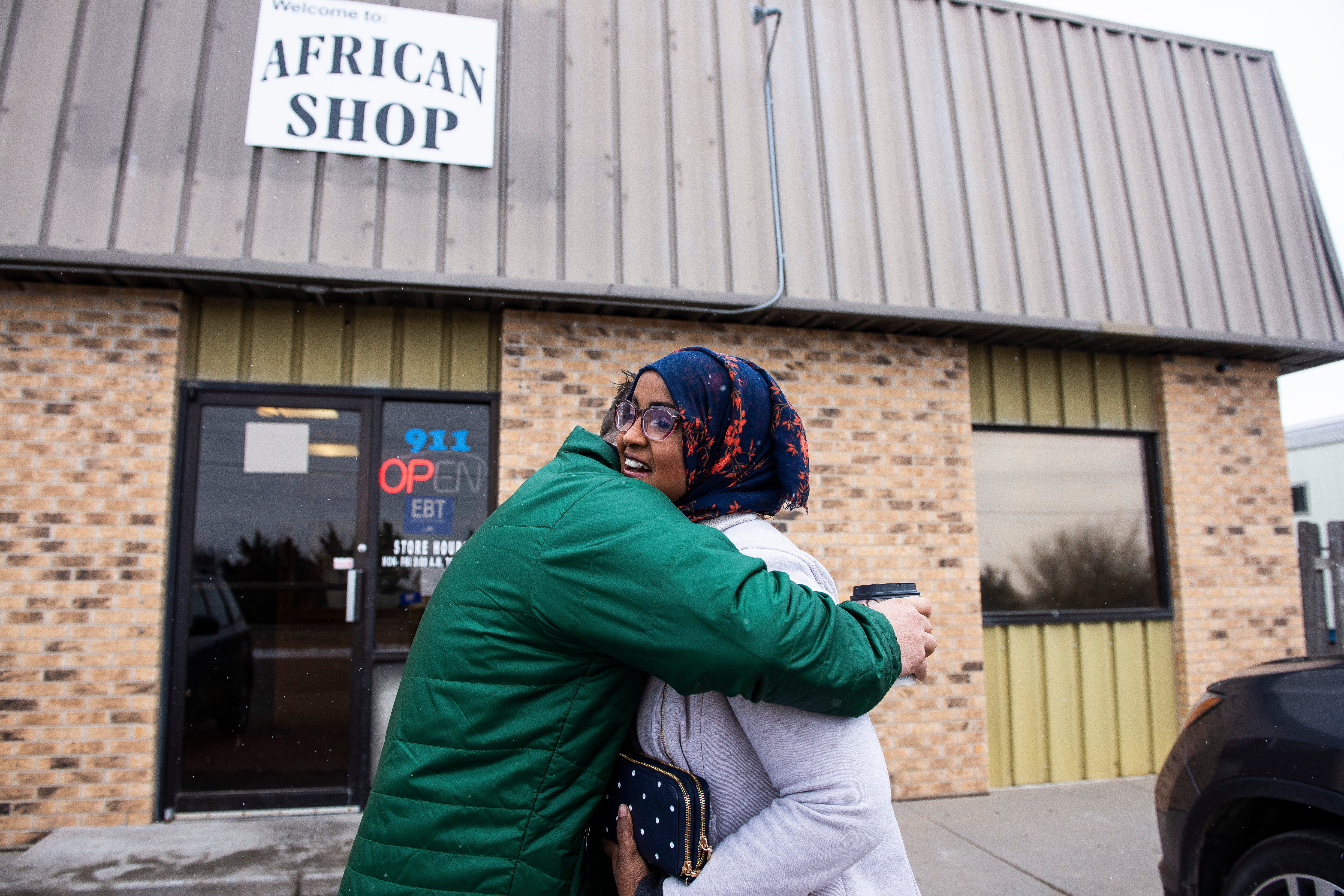 Kearny County Hospital CEO Benjamin Anderson, left, hugs Ifrah Ahmed outside the African Shop.