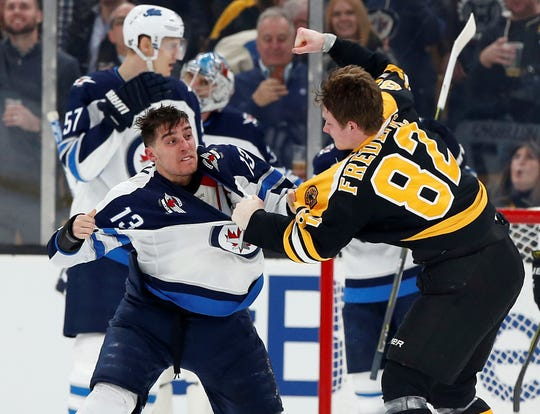 Boston Bruins center Trent Frederic, right, fights with Winnipeg Jets left wing Brandon Tanev during the second period at TD Garden.