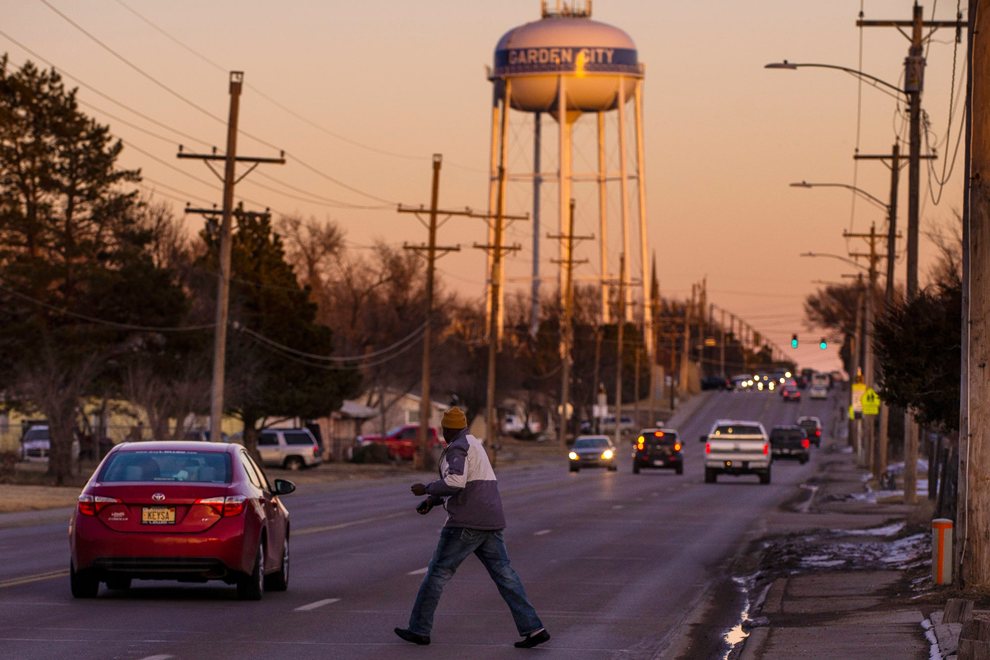 A man crosses the street between the Garden Spot apartments, which is home to about 100 Somali refugees on Wednesday, Jan. 23, 2019. In Garden City, population 27,000, residents speak 40 languages, including Burmese, Spanish, Vietnamese, Swahili and Creole. About 23 percent of the population is foreign born, according to the U.S. Census.