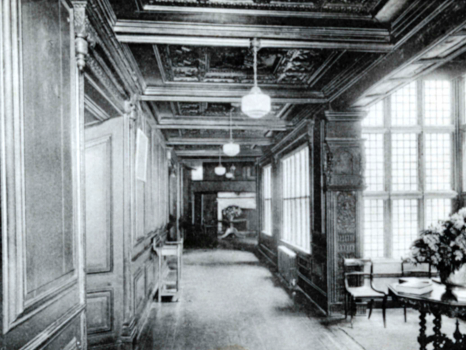Hopwood Hall's interior hallways as they used to look, circa 1920. The white fireplace mantle visible at the end of the corridor is dated 1688 and thought to have been a gift from the Romantic poet Lord Byron when he was a guest.
