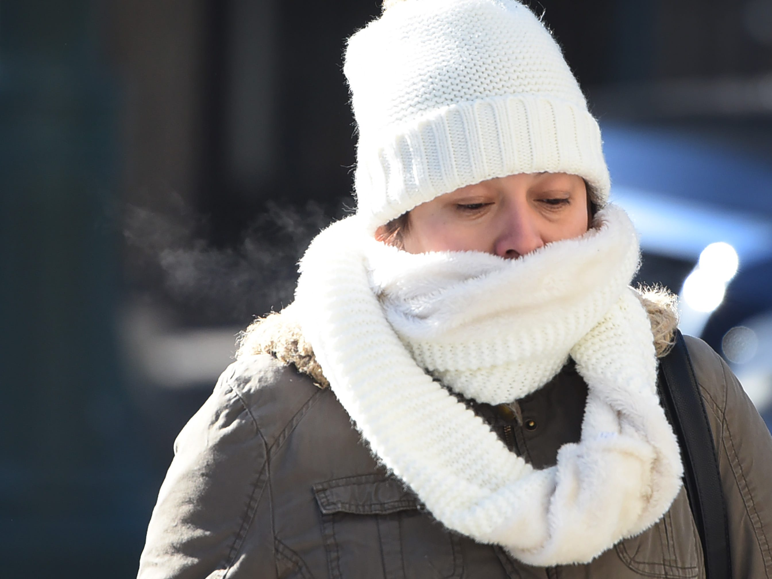 As the temperatures plummet, a woman braves the cold as she covers her face with a scarf in downtown Paterson, NJ., Jan. 30, 2019.