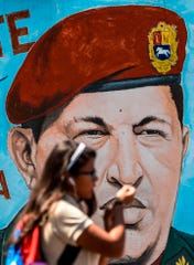 A student walks past a painting of late Venezuelan President Hugo Chavez on a wall in Caracas on January 29, 2019. - Venezuelan President Nicolas Maduro moved Tuesday to try to check the growing clout of opposition rival Juan Guaido as the United States tightened its stranglehold on the leftist regime's main source of revenues.
