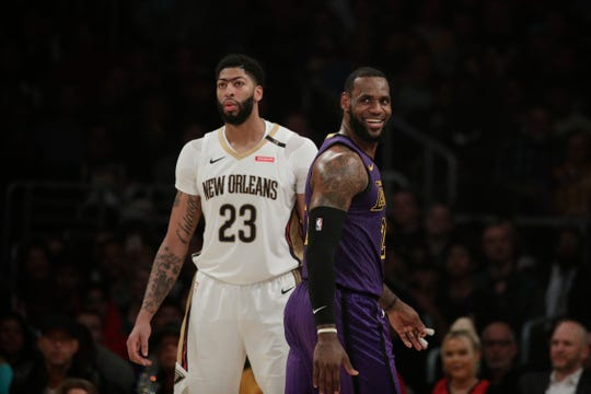 LeBron James smiles as he walks past Anthony Davis during a December game.