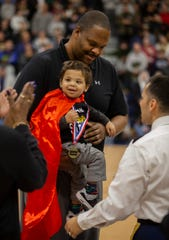 Ranney basketball coach Tahj Holden holds his son, Maxwell, during a halftime ceremony Wednesday night.