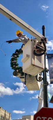 A city of Asheville worker removes a Christmas wreath in downtown Wednesday afternoon. The city is running late on decoration removal.