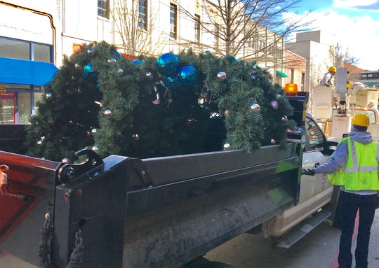 A city of Asheville worker loads a truck full of Christmas wreaths in downtown Wednesday afternoon. The city is running late on decoration removal.