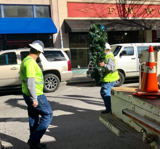 A city of Asheville worker carries a Christmas wreath in downtown Wednesday afternoon. The city is running late on decoration removal.