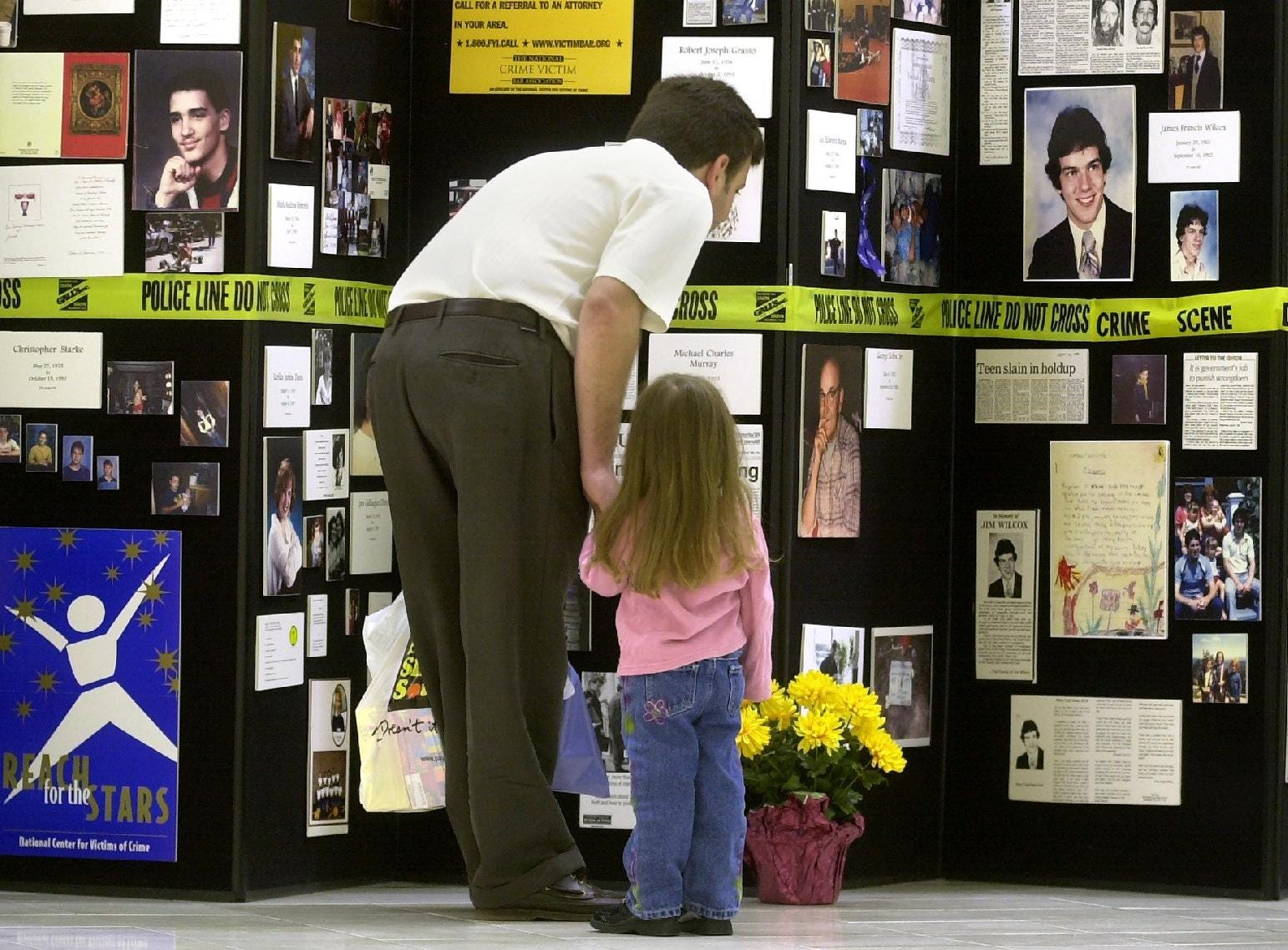 Dan Puglisi of Greene pauses while shopping at the Oakdale Mall Friday with his three-year-old daughter, Madison, to look at the Crime Victims Assistance Centeràs Remembrance Wall display in April of 2002.