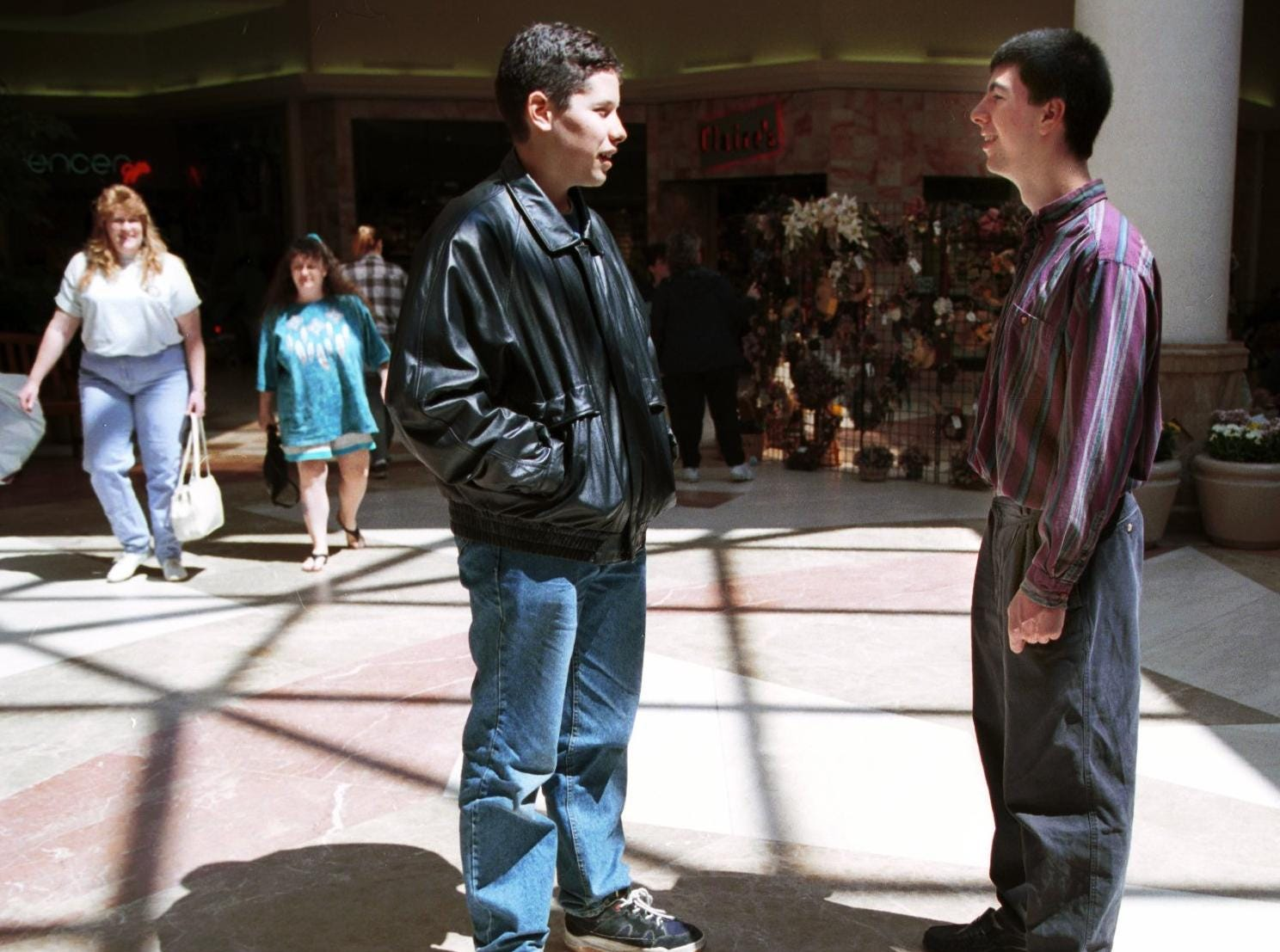 Anthony Holmes,17, (left) and Kyle Hyman,17, (right) talk in center court of the Oakdale Mall in April of 1999.