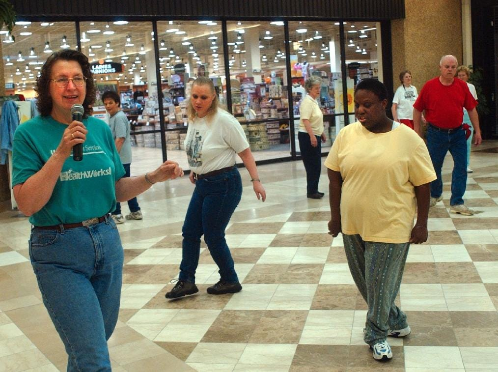 Joni Duff, left, gives out line dance instructions as Lisa Loveland, center, and Jamilla Darby of Binghamton watch Joni's foot steps at the Oakdale Mall in may of 2004.