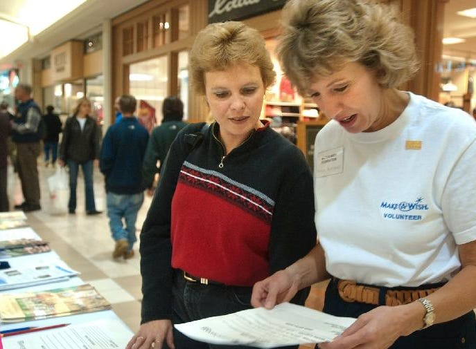 Chantal Lewis of Binghamton (left) speaks with Sandy Ruminski with the Make-A-Wish Foundation at the Oakdale Mall on about volunteering opportunites for her and her daughter on Oct. 26, 2003.