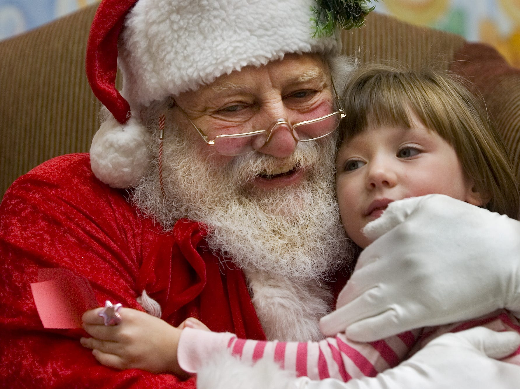 "Santa gives 4-year-old Hayley Laskowski, 4, of Vestal a hug while on duty with Gallery Photo at the Oakdale Mall on in December of 2007. Hank Eynard has been playing Santa for 15 years. ""Who can ask for a better job, it makes me so happy to see their faces,"" he said."