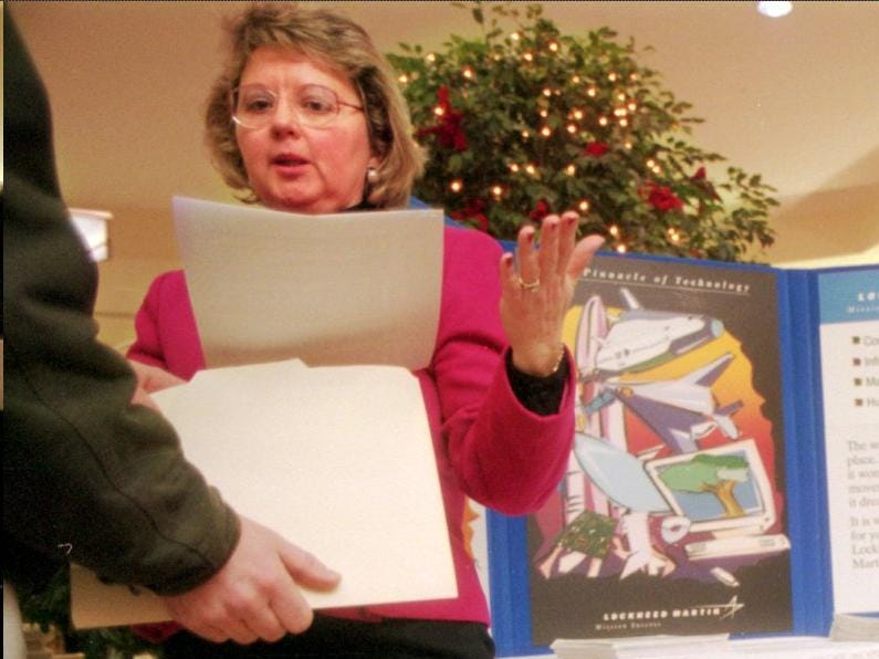Wanda Sierzant, administrative specialist with Lockheed Martin, takes resumes from prospective job candidates at the job fair at the Oakdale Mall on Dec. 29, 1997.