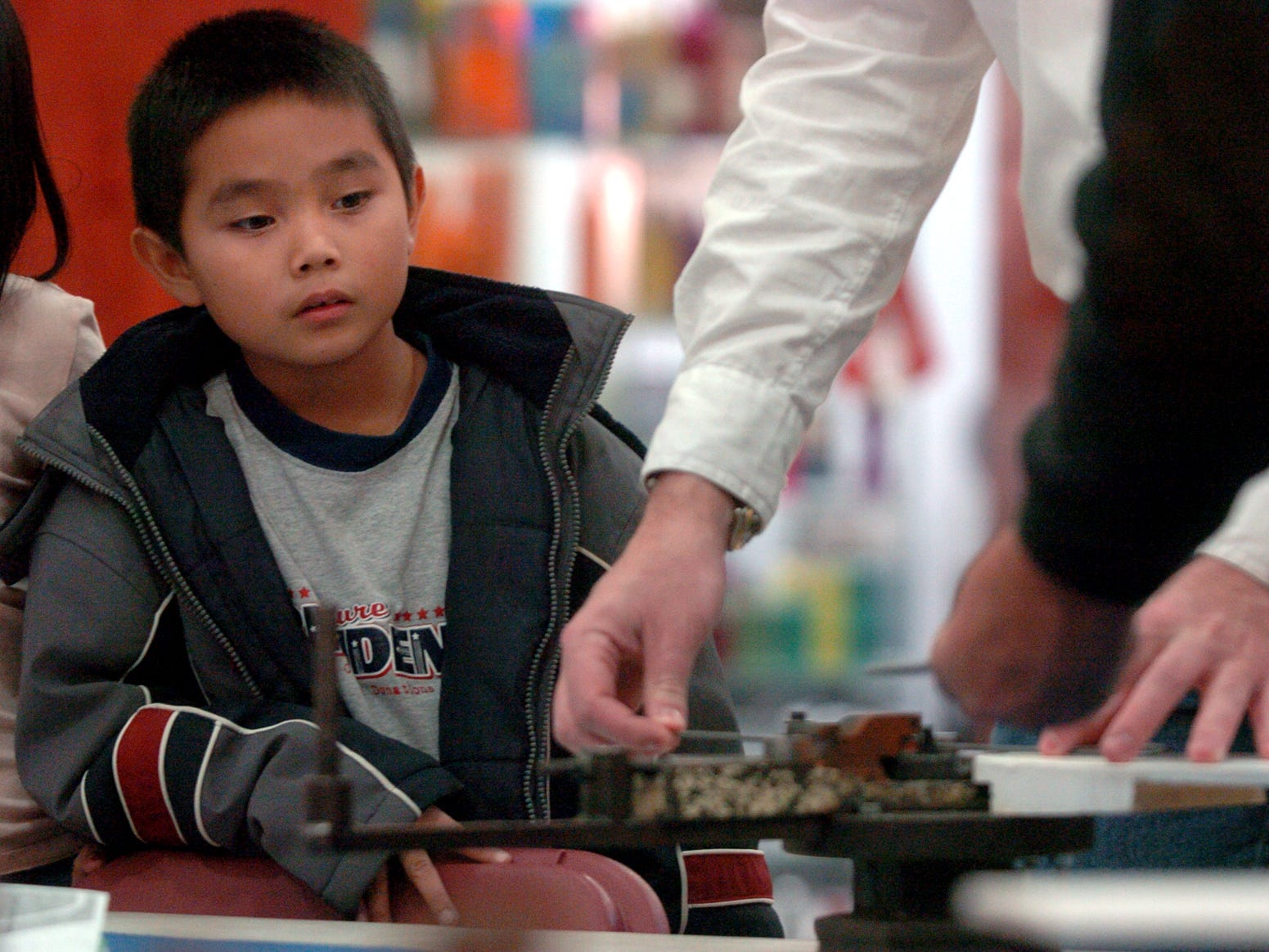 "Bryson Homsombat, 8, watches how a paper clip is made using a Diarco wire bending ""hand tool"" at a Center for Technology & Innovation, Inc., booth at the Oakdale Mall in Johnson City on Nov. 25, 2005."
