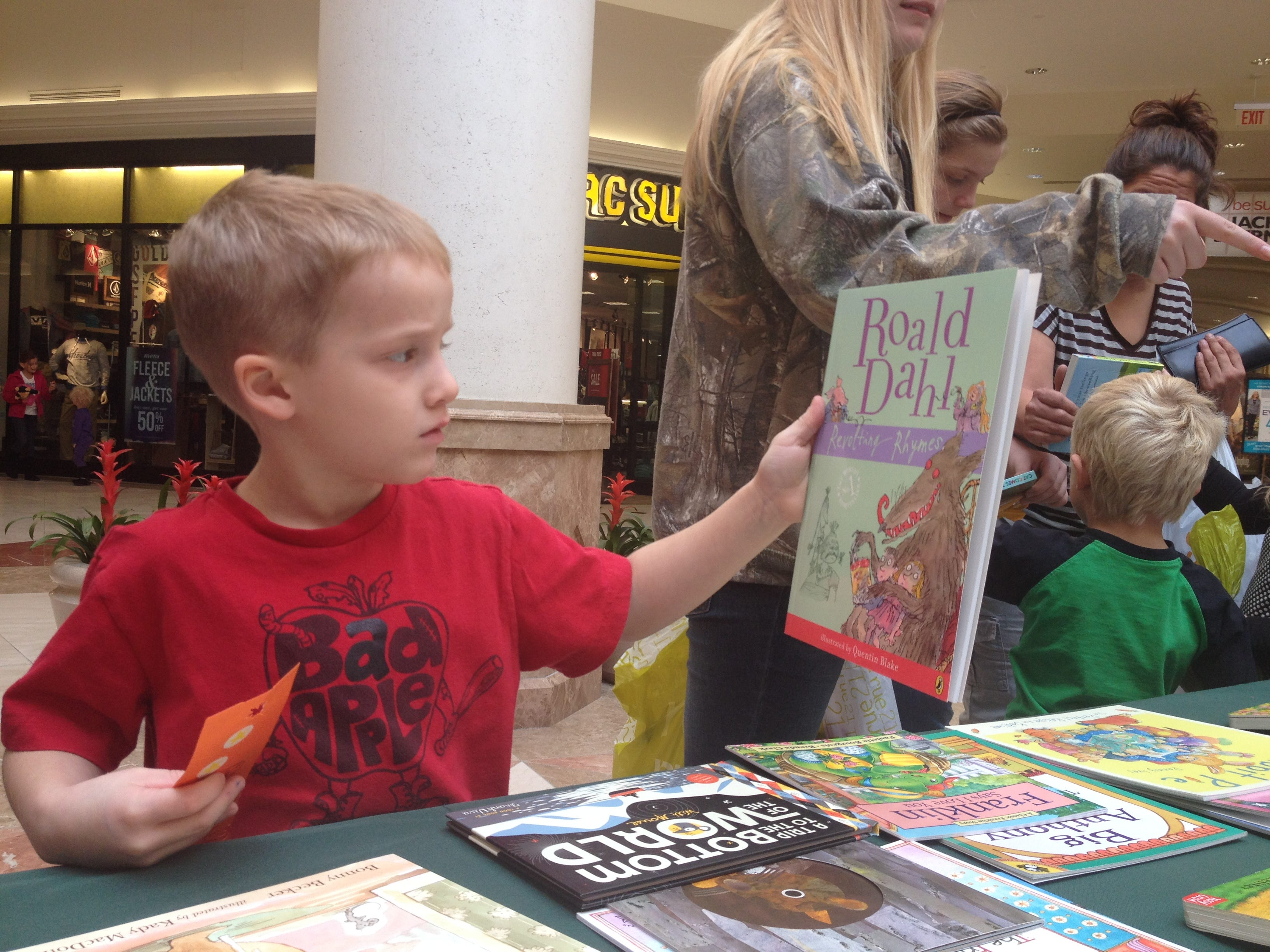 Wyatt Ide, 6, of Conklin, picks a book Saturday in the Oakdale Mall, where volunteers for the Four County Library System and the Press & Sun-Bulletin encouraged reading in October of 2013.