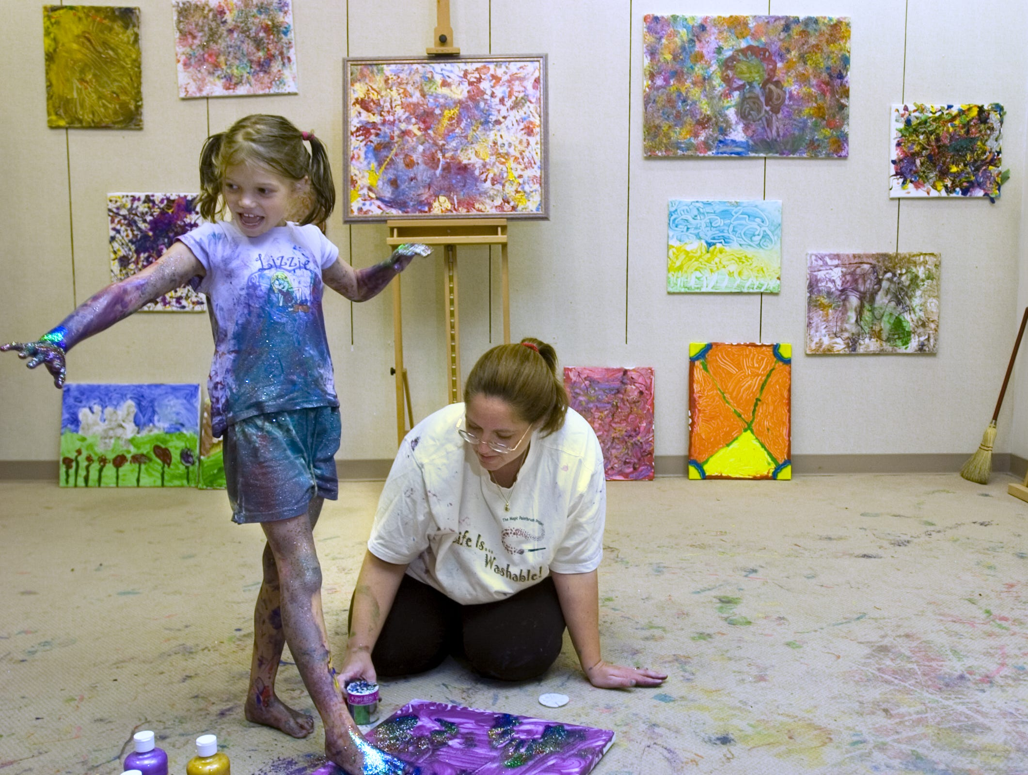Shannon Wheeler, 8, admires her paint and glitter covered hand as The Magic Paintbrush Project coordinator Jennifer O'Brien adds a footprint to Shannon's painting in August of 2006. In the background are the works of other special needs visitors to the project's Oakdale Mall space.
