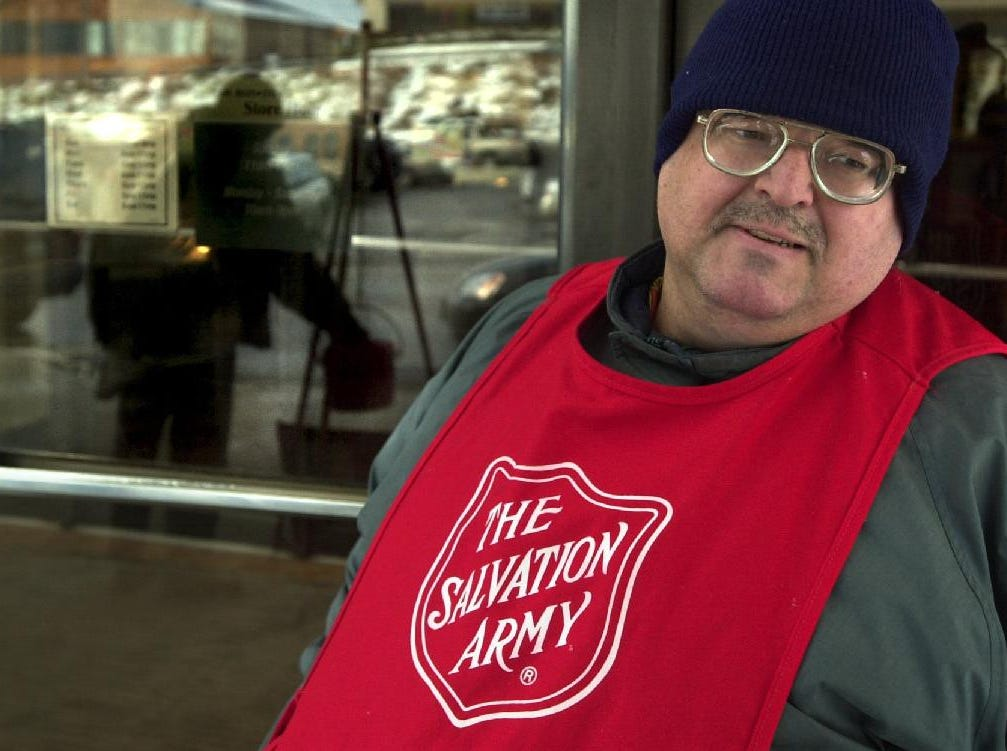 Salvation Army bell ringer Peter Scott holds the door to the BonTon store at Oakdale Mall as another mall visitor, reflected in the door's glass at left, drops a contribution into the kettle on in December of 2003. His bell is different from those of other Salvation Army bell ringers - he salvaged it from the garbage, cleaned it, and gave it a fresh coat of gold paint.