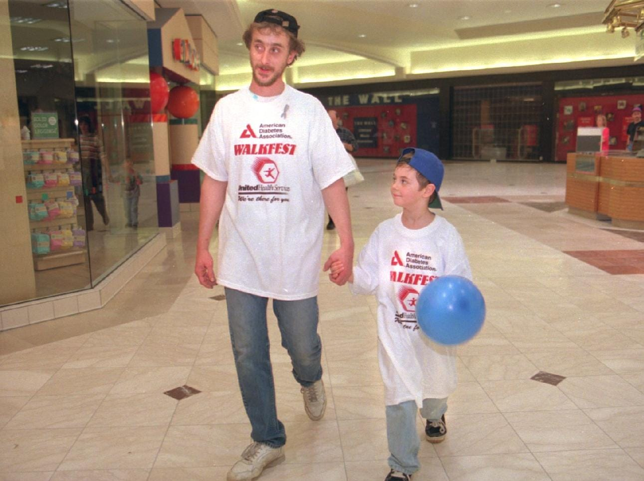 Ray and his son Bradly Glover,8, of Maine stroll the Oakdale mall to fight diabetes as part of the American Diabetes Association Walkfest in March of 1998.