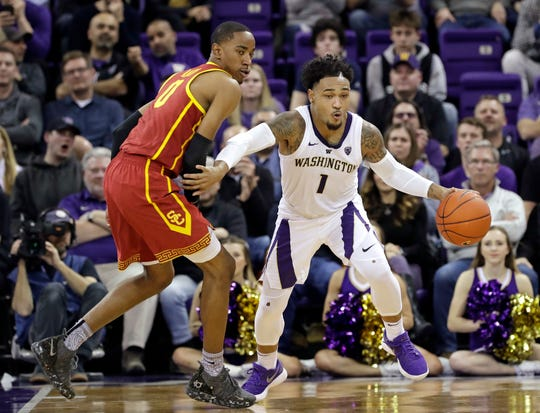 Washington's David Crisp (1) races past Southern California's Shaqquan Aaron during the second half of an NCAA college basketball game Wednesday, Jan. 30, 2019, in Seattle. Washington won 75-62.