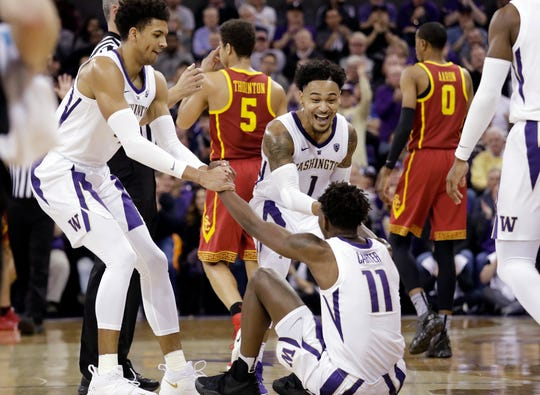 Washington's Matisse Thybulle, left, and David Crisp (1) rush to help up Nahziah Carter (11) after Carter was fouled by a Southern California player during the first half of an NCAA college basketball game Wednesday, Jan. 30, 2019, in Seattle.