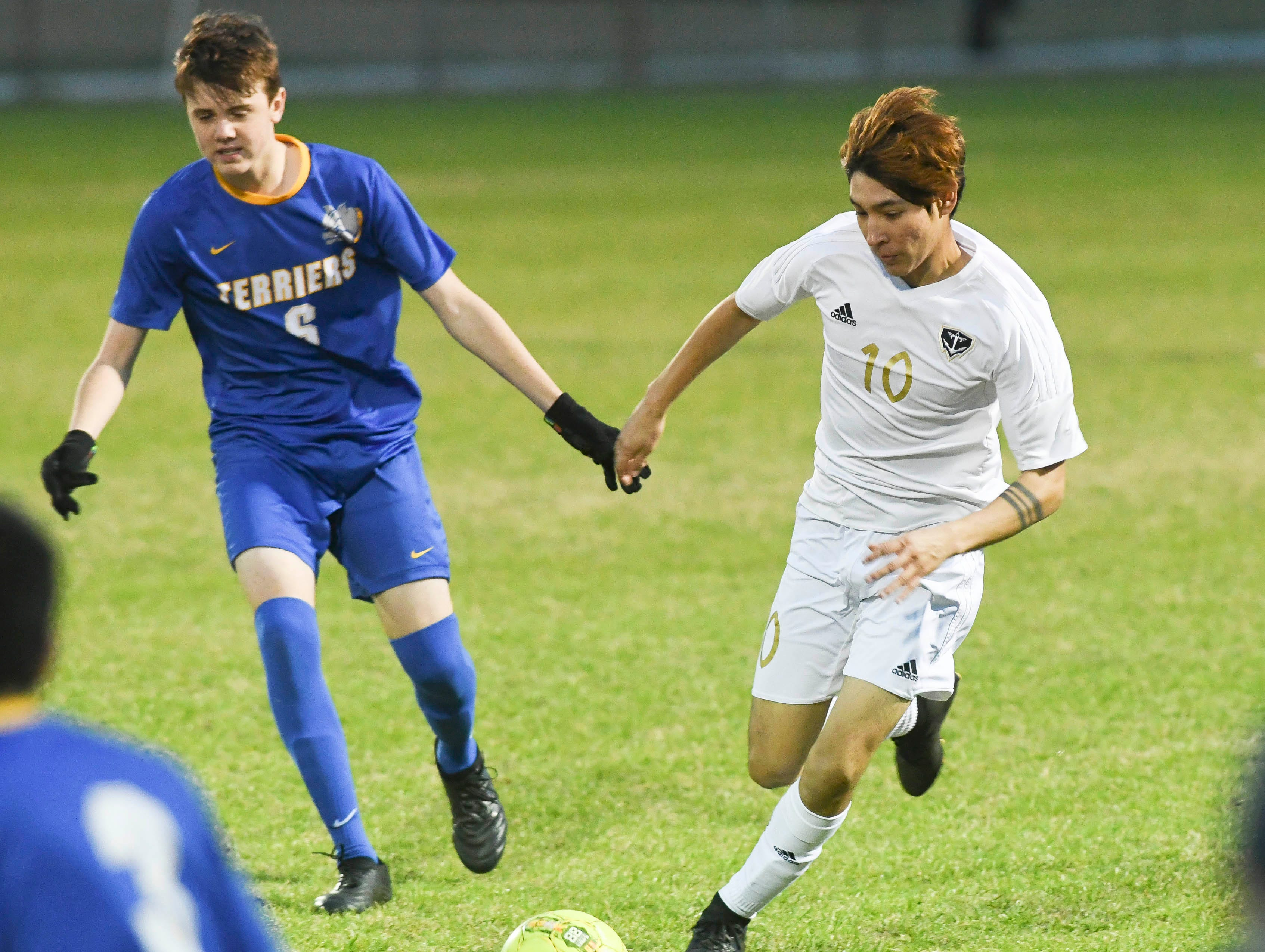 Eau Gallie's Jesus Rascon (10) is pursued by Josh Fox of Titusville during Wednesday's District 12, Class 3A semifinal at McLarty Stadium