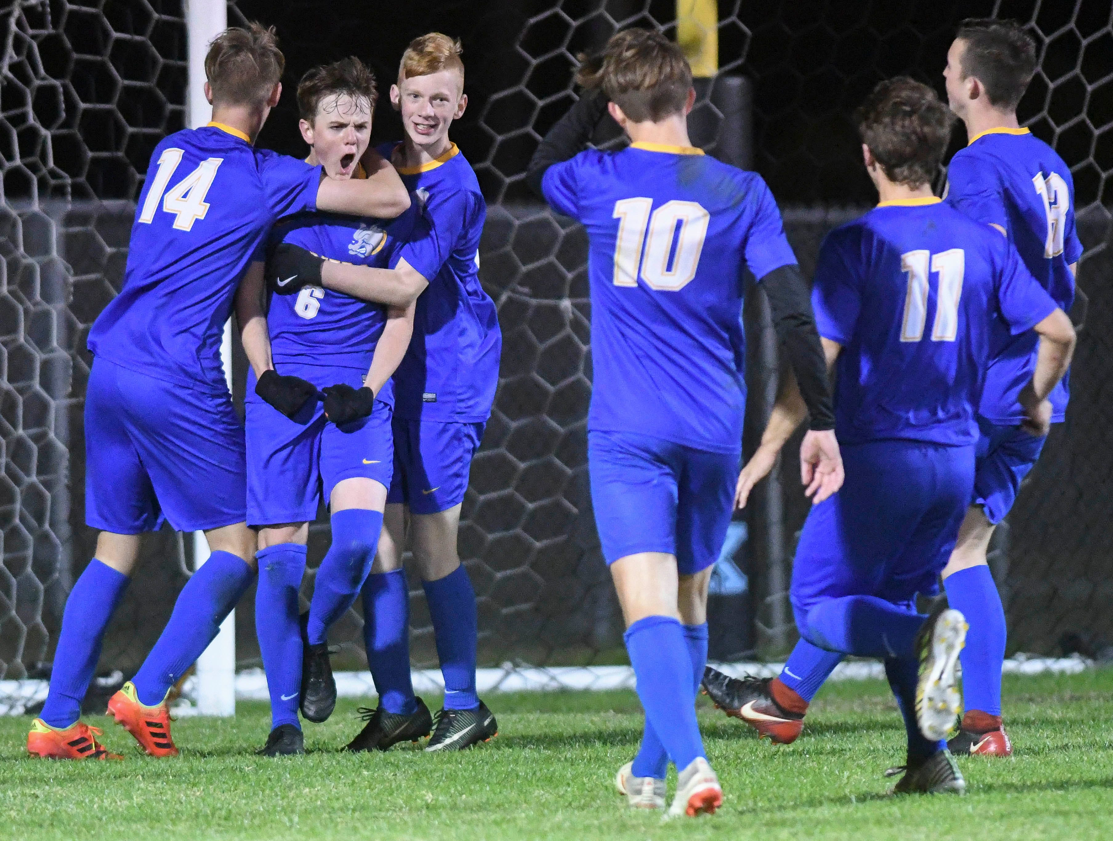 Titusville teammates congratulate Josh Fox (6) after he scored in Wednesday's District 12, Class 3A semifinal at McLarty Stadium