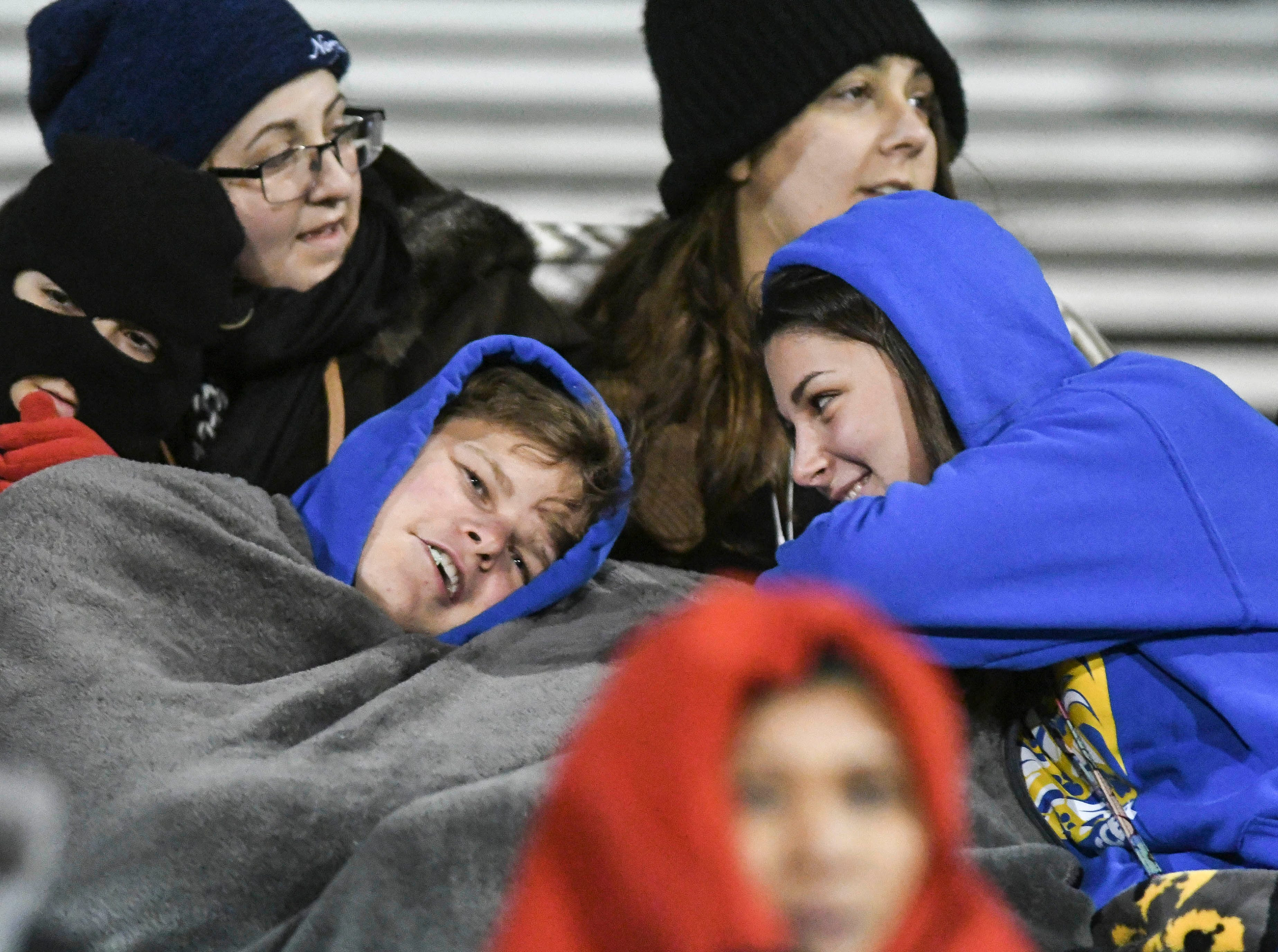 Spectators bundle up against the cold during Wednesday's District 12, Class 3A semifinal at McLarty Stadium